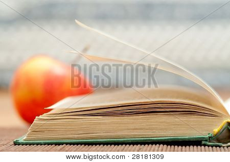 Open book and blurred apple