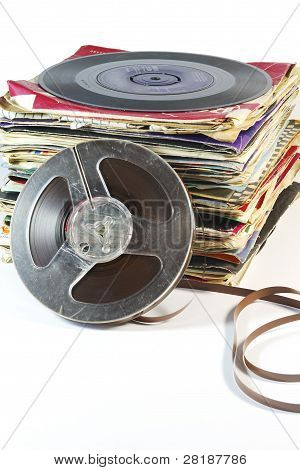 Pile of old vinyl records with a reel to reel tape