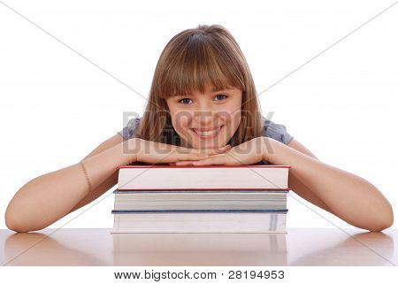 Girl Sits At Table And Has Put Hands On A Pile Of Books.