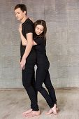 Pretty Young Dancer Hugging Her Partner. Young Dancers In Black Suits Posing On Studio Background. T poster