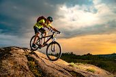 Cyclist Riding the Mountain Bike on the Rocky Trail at Sunset. Extreme Sport and Enduro Biking Conce poster