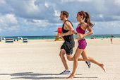 Running people jogging exercising on South Beach, Miami, Florida. Man and woman training partner run poster