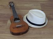 A Cavaquinho (a Small Brazilian String Musical Instrument) And A Samba Player (sambista) Hat On A Wo poster