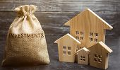 Money Bag With The Word Investments And Wooden Houses. The Concept Of Attracting Investment In Real  poster