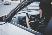 Woman Using Navigation App On Smartphone While Driving A Car. Side View Of Brunette Girl Sitting In  poster