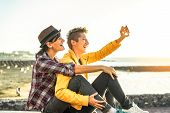 Happy Gay Couple Taking A Selfie With Mobile Smart Phone Camera On The Beach At Sunset - Lesbians Ha poster