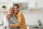 Elderly Woman With Female Caregiver In Kitchen. Space For Text poster