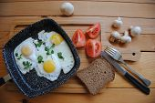 Fried Eggs In A Pan With Tomatoes And Bread For Breakfast On A Wooden Background. Tasty And Healthy  poster