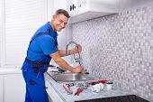 Side View Of A Plumber Fixing Water Tap In Kitchen poster