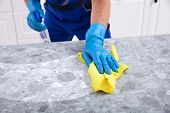 Mid Section Of A Male Janitor Cleaning Dirty Kitchen Counter With Spray Bottle And Napkin poster