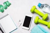 Fitness And Healthy Lifestyle Concept. Dumbbells, Measuring Tape, Water And Smartphoneon Light Backg poster