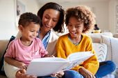 Close up of young mother sitting on sofa in the living room with her children, reading them a book,  poster