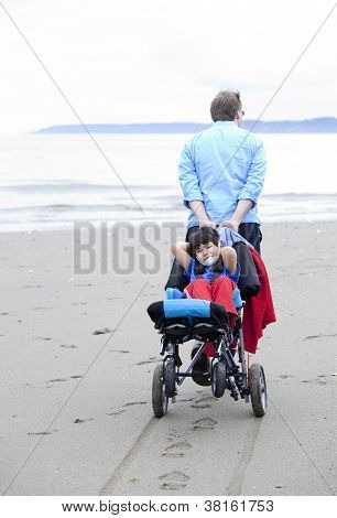 Father Pulling Disabled Son On Wheelchair Through The Beach Sand