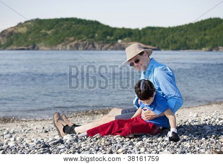 Father Sitting On Beach Playing With Disabled Son