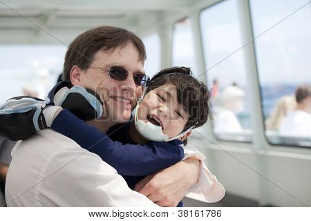Father Hugging Disabled Son As They Ride A Ferry Boat