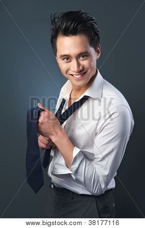 Handsome Smiling Businessman Fixing Tie