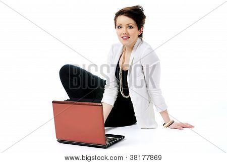 Young woman smiling sitting on the floor with laptop