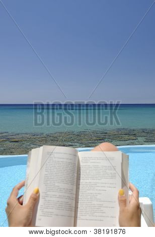 Girl reading a book over the sea