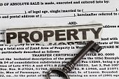 stock photo of deed  - Property abstract for deed of sale with a vintage key in the foreground - JPG