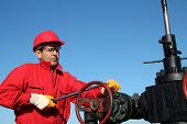 stock photo of crude  - Worker in action at pump jack oil well - JPG