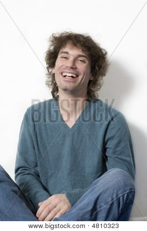 Portrait Middle-age Smiling  Curl Man Sitting. White Background
