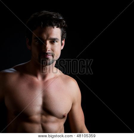 Low key portrait over black of an athletic young man with naked torso, looking directly to the camera.