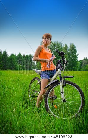 Young Woman On Bike Drinking Water From A Bottle