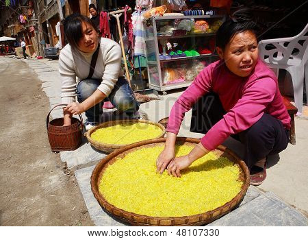 Dong Ethnic Women Treated With Rice On A Street Zhaoxing Dong Village. Yellow Rice Is Found In Large