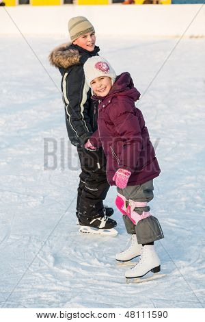 Boy and girl skating on rink hand in hand in winter, focus on a girl