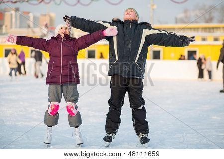 Boy and girl skating on rink and making hands to the side