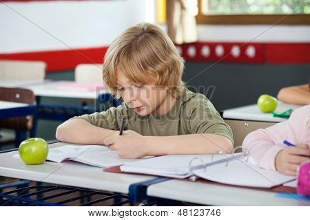 Little schoolboy writing on book with apple at desk in classroom