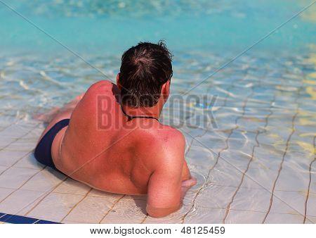 Back Side Of Man Resting In Blue Swiming Pool