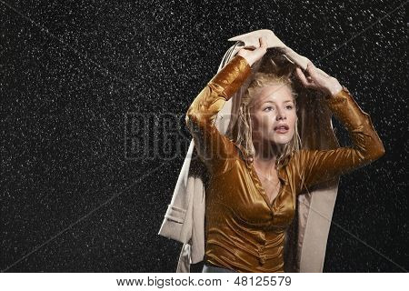 Young businesswoman covering head with jacket during rainstorm