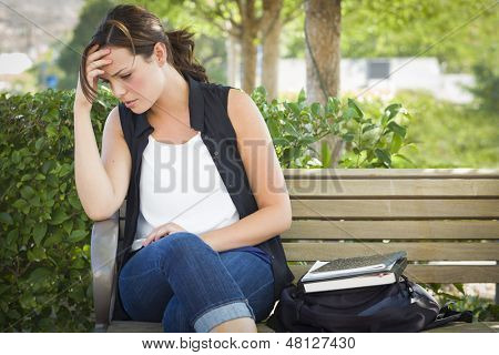 Upset Young Woman Sitting Alone with Her Head in Her Hands on Bench Next to Books and Backpack.