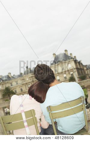 Rear view of a woman leaning head on man's shoulder against building