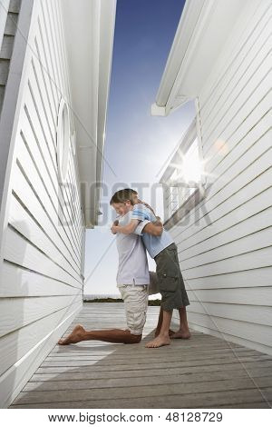 Side view of happy father hugging son in passageway between beach houses