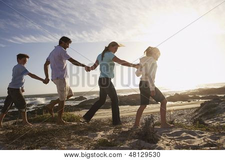 Side view of parents and children walking hand in hand on beach
