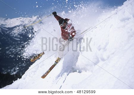 Side view of a male skier skiing through powdery snow on ski slope