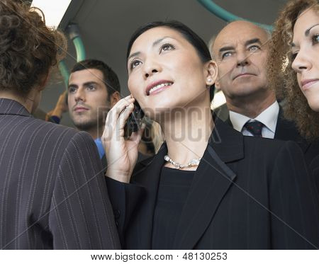 Closeup of a businesswoman using mobile phone in train amid commuters
