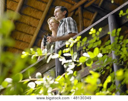 Low angle view of a couple on terrace with binoculars