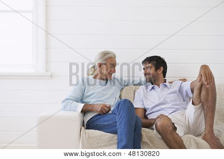 Senior man conversing with son on sofa at home