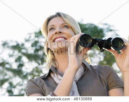 Closeup low angle view of a smiling woman with binoculars outdoors