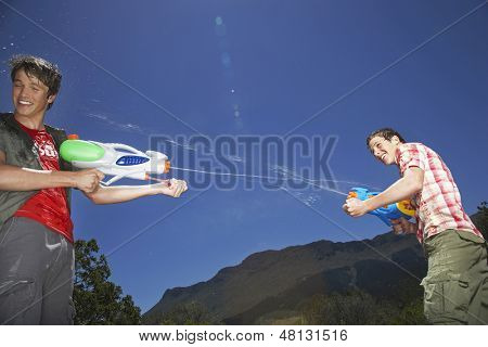 Two teenage boys fighting with water guns in mountains