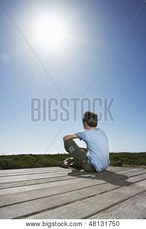 Vista posterior del niño sentado en el Malecón contra un cielo claro