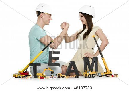 Team building concept: Smiling young man and woman building the word team along with construction machines, isolated on white background.