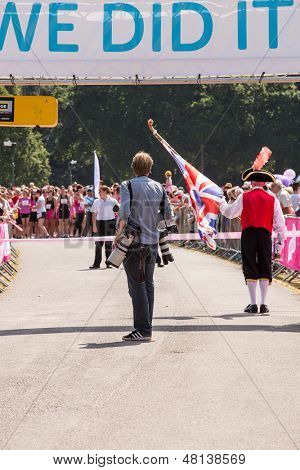SOUTHAMPTON, UK - JULY 14: Press photographer and Town Crier at the start of the annual Race for Life, where women run to raise money for Cancer Research. 14 July 2013