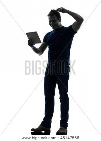 one caucasian man holding digital tablet  brushing hair  in silhouette on white background