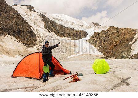 O alpinista em pé perto da tenda na geleira