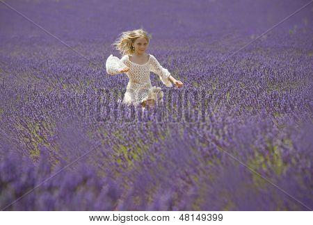 Happy little girl jumps in field of lavander