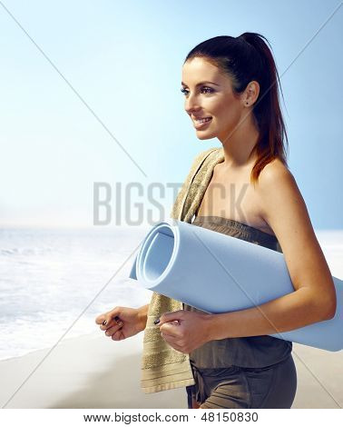 Attractive young woman on the coast, holding beach mattress, smiling happy.